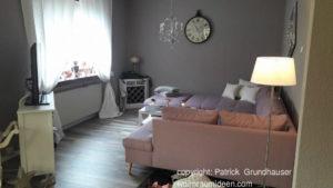 Schicke EInrichtung, rosa-lila Sofa graue Wände, viel Weiß