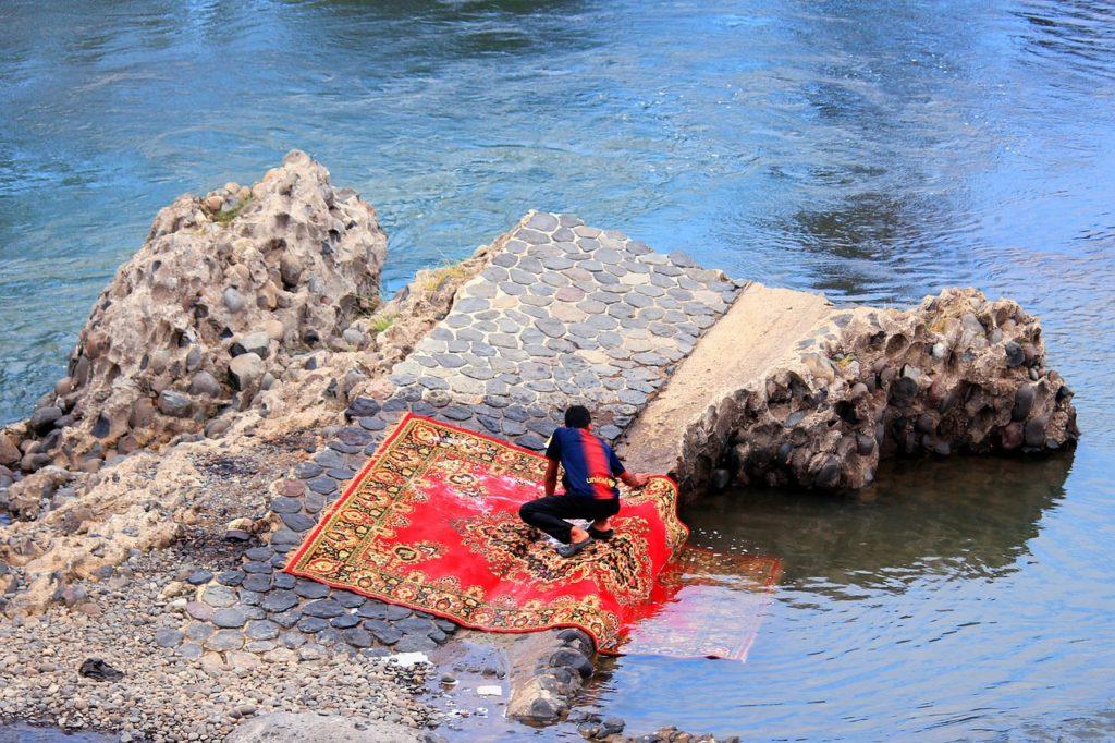 Mann reinigt Teppich im Meer
